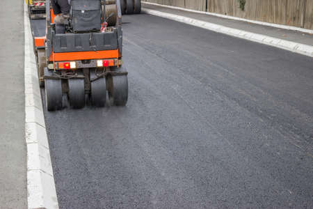 asphalting: mini compactor roller during road construction at asphalting work