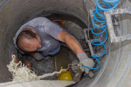 Ein Mann in Mannloch auf der Straße, mit einem Luftkompressorschlauch für Reparaturen in einem Schacht Standard-Bild - 24032099