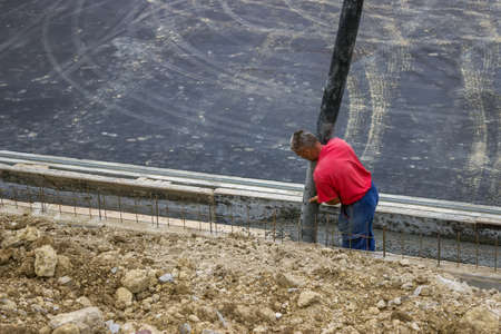 Worker pouring concrete on retaining concrete Wall, aiming pump tube during concrete pouring  Standard-Bild