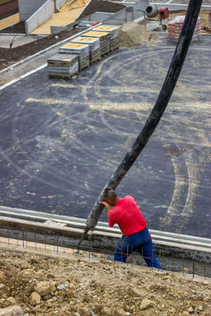 Worker pouring concrete on retaining concrete Wall, aiming pump tube during concrete pouring  photo