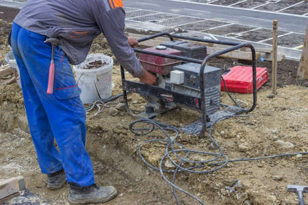 Construction Worker starts the portable Electric Generator at the building site photo