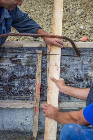 serrucho: tabla para cortar madera con una sierra de mano artesano Foto de archivo