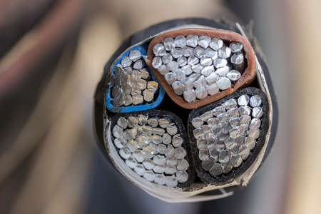 coax: Cross section of black industrial underground cable on large wooden reel. Four core al cable. Selective focus and shallow dof.