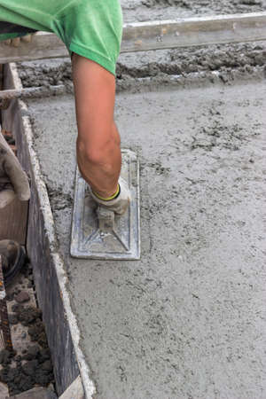 Concrete leveling with trowel, spreading poured concrete. Selective focus.
