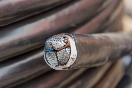 Cross section of black industrial underground cable on large wooden reel. Four core al cable. Selective focus and shallow dof.