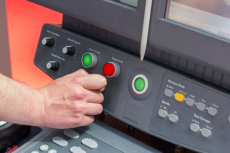 programmable: Close of hand using control panel of a cnc machine. Programmable machine. Selective focus and shallow dof.