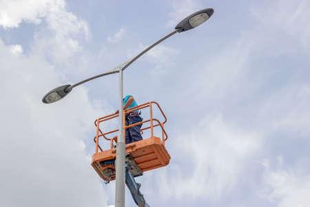 werknemer in de lift emmer reparatie straat licht paal met dubbele kop
