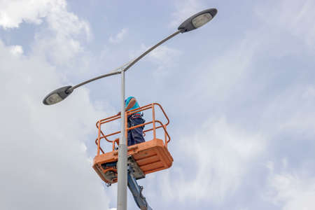 worker in lift bucket repair street light pole with double head