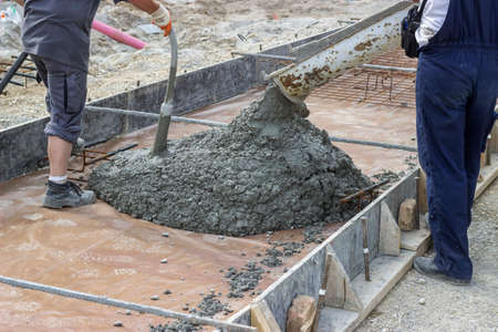 Use concrete vibration generator during concreting supports for the tram tracks. Pouring works with removal air bubbles for maximum strength and consistency in concrete. Selective focus. Stock Photo