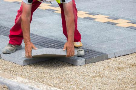 Mason hands laying paver bricks, paver making sidewalk. Selective focus and shallow dof.