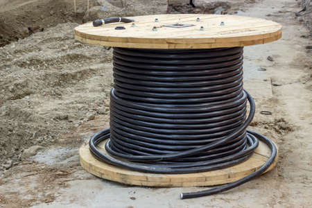 Roll of black industrial underground cable on large wooden reel at construction site. Four core al cable. Selective focus and shallow dof. 免版税图像