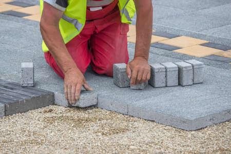 paver: Mason hands laying paver bricks, paver making sidewalk. Selective focus and shallow dof.