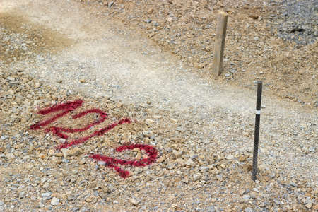 Geodetic survey marks and red tag on a road construction project. Selective focus.