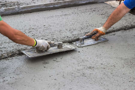 slabs: Leveling concrete with trowels, mason hands spreading poured concrete. Selective focus.