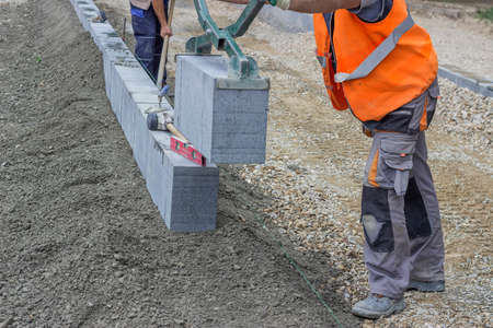kerb: Installation of granite curb, vertical curbing. Selective focus and shallow dof.