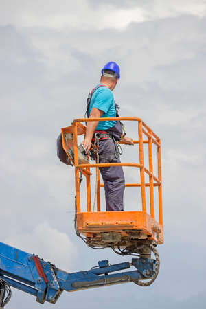 Electrical worker in lift bucket during installation street light pole. Selective focus and shallow dof. photo