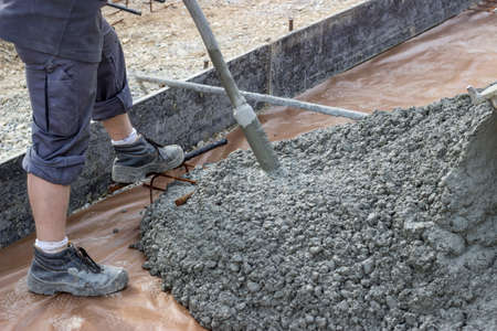 compaction: Vibrating air poker, used to remove entrained air in poured concrete. Compaction and removal of air bubbles for maximum strength and consistency in concrete.