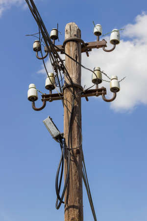 Wooden electrical pole with telephone lines with sky background Stock Photo