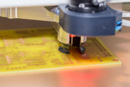 CNC drill machine drilling a printed circuit board. Drilling PCB holes. Selective focus and shallow dof.