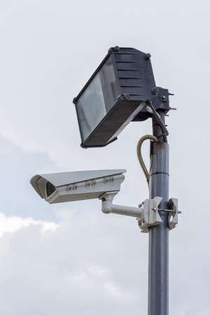 larceny: Security industries camera surveillance systems. Surveillance camera and lighting on plain pole.