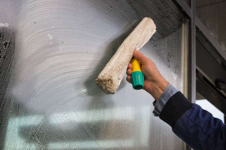 machine à laver: Nettoyage des vitres à la main d'un bâtiment, laver une fenêtre Banque d'images