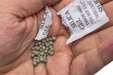 opened packet of silica gel in hand
