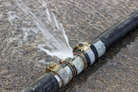 unsustainable: Water loss from rubber line tube. Bad pipe connection, pipe leak. Stock Photo
