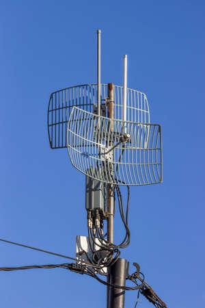 antennas: Outdoor wireless parabolic directional antennas on pole, grid antennas Stock Photo