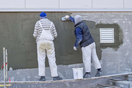 Workers plastering a outdoor wall with trowel.