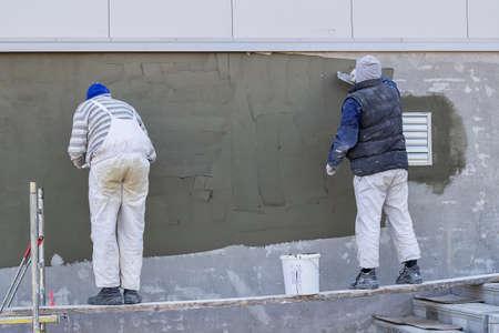 Workers Verputzen eine Außenwand mit Kelle Standard-Bild - 41379567