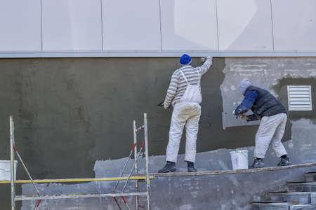 steeplejack: Workers plastering a outdoor wall with trowel