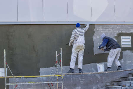 Workers plastering a outdoor wall with trowel