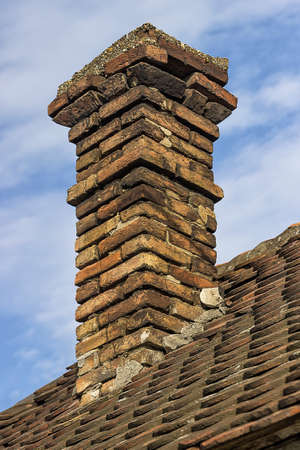 Old brick chimney with old tiles roof on a family house