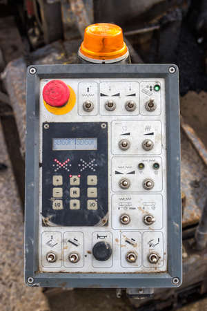 asphalting: close of a control panel of asphalt paving machine  at road construction site.