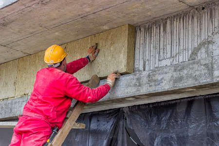 Man installing external wall insulation, mineral rockwool board insulation at construction site. Selective focus.