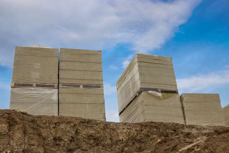 Stacks of mineral rock wool board insulation at construction site. Selective focus.