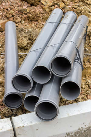 Stacks of pvc pipes at construction site. Selective focus.