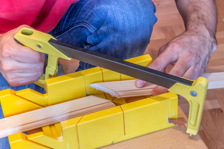 miter: Using hand saw and miter box for 45 degree cutting.