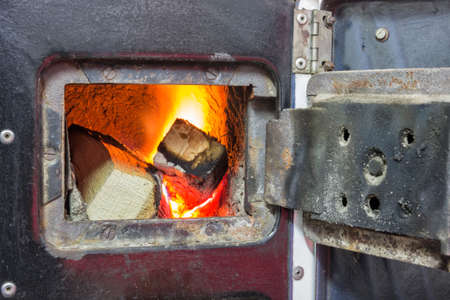 firebox: Wood stove firebox with fire and wood. Burning fire in fireplace. Stock Photo