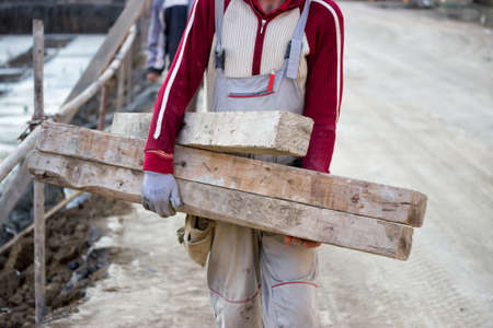 steeplejack: Worker carrying wooden beam for formwork at construction site
