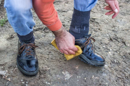 dirtiness: Worker cleaning shoes with sponge after work. Selective focus. Stock Photo