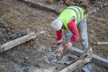 stake: Worker with ax making wooden stakes at construction site. Making stake that holds the form vertical.