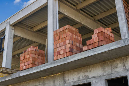 brick house: Stacked red hollow clay blocks for building block walls at construction site. Selective focus.
