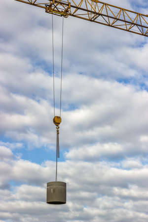 sewer pipe: lifting concrete sewer pipe by crane at the building site  with sky in background