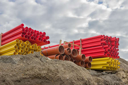 Stacks of various colored pvc pipes at construction site