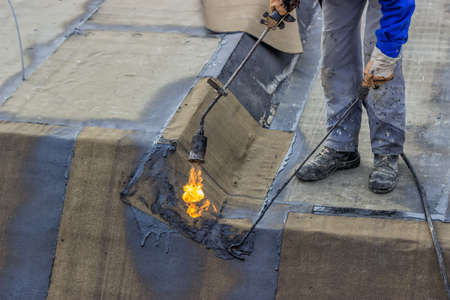 Insulation worker and propane blowtorch at floor slab waterproofing works. Worker heating and melting bitumen felt. At construction site. Selective focus.
