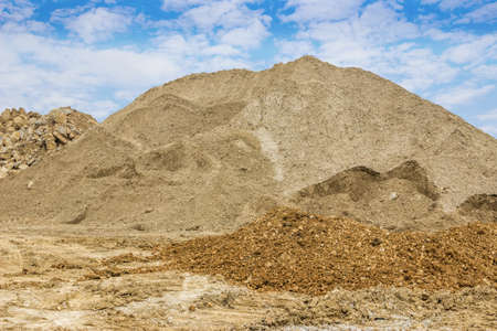construction material: Piles of sand and stone at the a construction site. Piles of construction material.