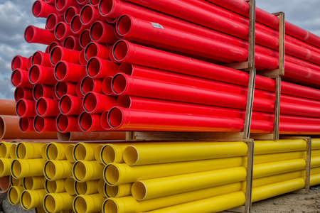 canalization: Stacks of various colored pvc water pipes at construction site Stock Photo