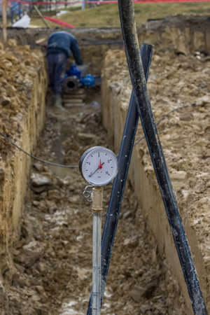 red  pointer: Water pressure gauge for pressure testing of water main. The red pointer show the highest pressure reached. Stock Photo