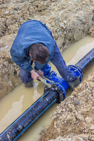 Worker installing water pipe valve in a trench. Laying a water pipeline. Selective focus. At construction site.